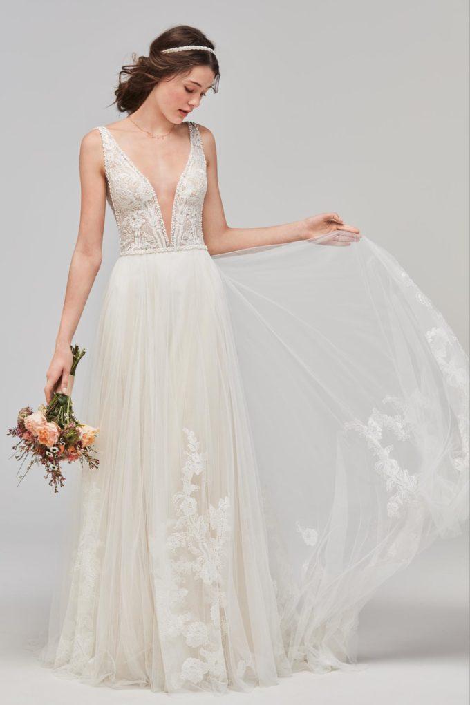 Braut mit Schleppe und Brautstrauß in der Hand
