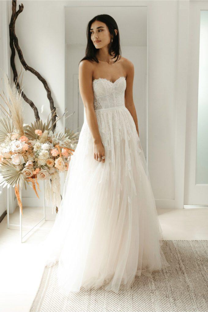 Braut mit einem Brautkleid mit Blümchenapplikationen