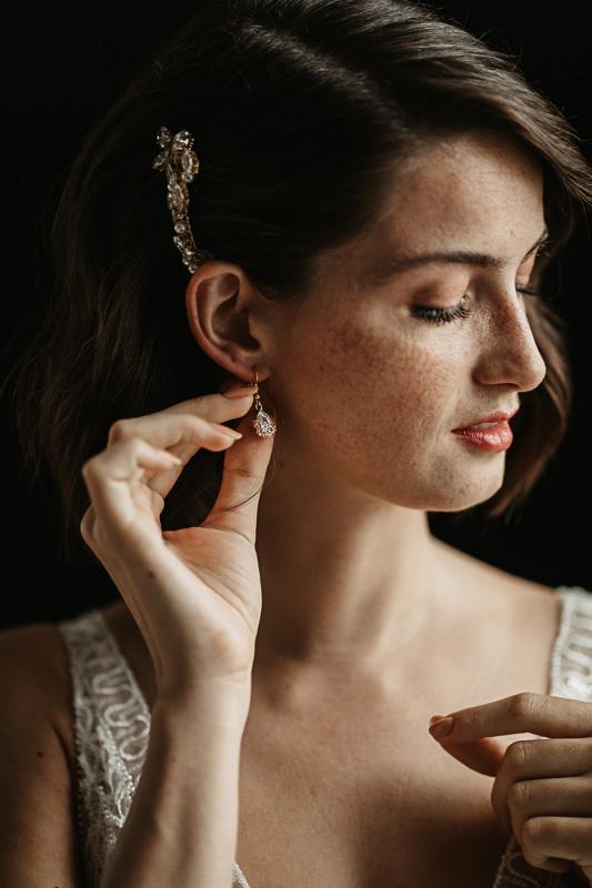 Braut zieht Ohrringe an